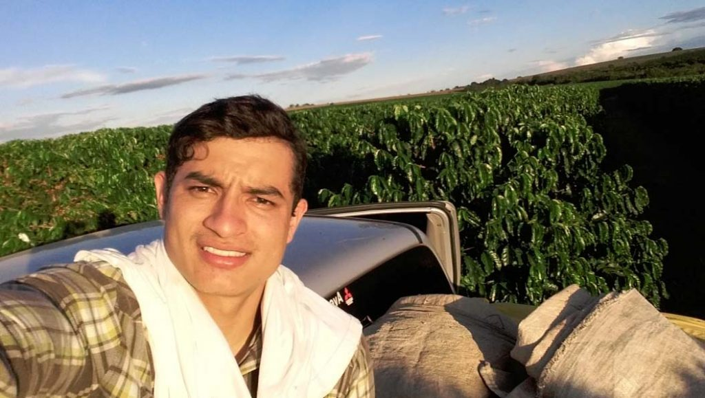 Heiber Andres Trujillo Samboni in the coffee fields. Selfie of a young man that is standing of the back of a pickuptruck full of bags. In the background you can see coffee plants.